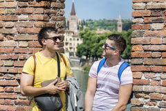 Friends talking outdoor. Portrait of two smiling young men talking and gesticulating in Italy stock photo