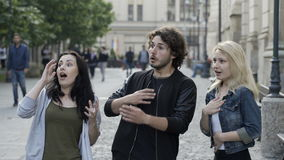 Friends talking outdoor in public urban street surprisingly having a scared reaction. Teenagers friends talking outdoor in public urban street surprisingly stock video