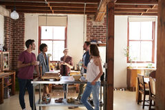 Friends talking over coffee in kitchen, three quarter length Royalty Free Stock Photos