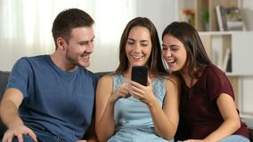 Friends talking about phone content at home. Front view of three happy friends talking about smart phone content at home sitting on a couch