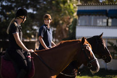 Friends talking while sitting on horse at barn Royalty Free Stock Image