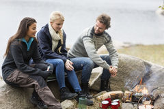 Friends Talking While Sitting On Rock During Camping Stock Photos