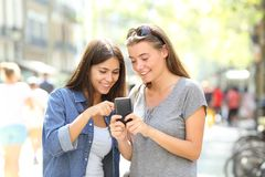 Friends talking about smart phone content. Two happy friends talking about smart phone content in the street Stock Image