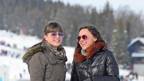 Friends talking and smiling in winter. Two female friends are having fun talking and smiling in winger snow mountain stock video footage