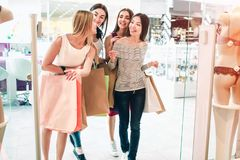 Friends are talking among themselves and walking into lingerie store. They are holding bag. Girls are shopping and. Having some fun Stock Photos