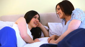 Friends talking together. While lying on a bed stock footage