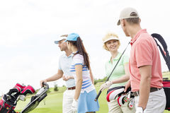 Friends talking while walking at golf course against clear sky Royalty Free Stock Photo