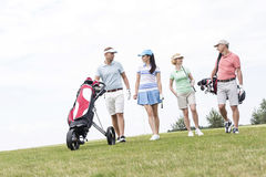 Friends talking while walking at golf course against clear sky Royalty Free Stock Photos