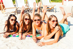 Friends tanning in beach bar on sand Stock Image