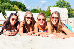 Friends tanning in beach bar on sand royalty free stock photos