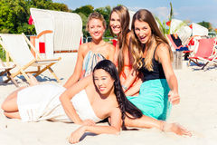 Friends tanning in beach bar on sand stock images