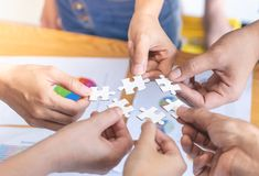 Friends team joining puzzle together for business concept stock image