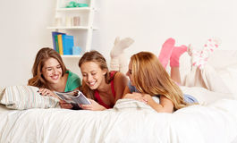 Friends or teen girls reading magazine at home Royalty Free Stock Photography
