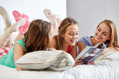 Friends or teen girls reading magazine at home Royalty Free Stock Images