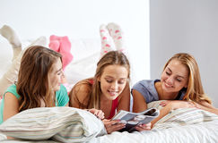 Friends or teen girls reading magazine at home Stock Image