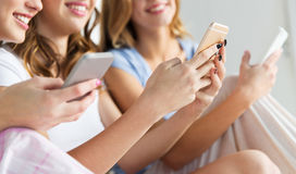 Friends or teen girls with smartphones at home Stock Photo