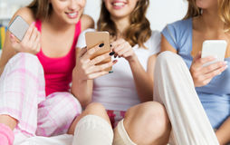 Friends or teen girls with smartphones at home Royalty Free Stock Image