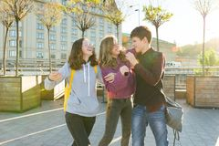 Friends teenagers students with school backpacks, having fun on the way from school royalty free stock image