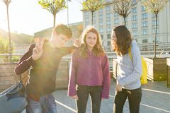 Friends teenagers students with school backpacks, having fun on the way from school royalty free stock photos