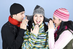 Friends telling secrets and laughing. Three friends having fun,two of them trying to tell a secret to girl in middle at her cap ears and all laughing together Stock Images