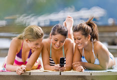 Friends text messaging. With cell phone Royalty Free Stock Image