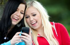 Friends texting on cell phone Royalty Free Stock Photography