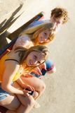 Friends man and women using mobile phones. Friends texting using mobile phones outdoor. Young women and men browsing internet on smartphone. Summer relax Stock Photos