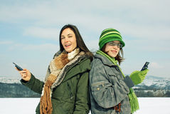 Friends texting in winter  Stock Photos