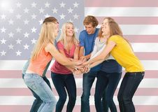 Friends with their hands stacked against american flag in background Stock Photo