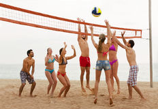Friends throwing ball over net and laughing Stock Photo
