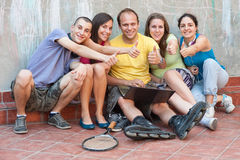 Friends with thumbs up. Group of five young people, sitting outside after some activity, using a laptopt computer, smiling, holding their thumbs up Stock Photography