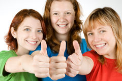 Friends with thumbs up. Portrait of young woman with teenage friends making thumbs up sign, isolated on white background Royalty Free Stock Images