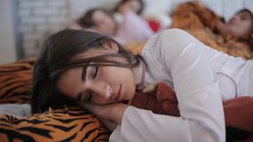 Friends tired after the party, sleeping together on the bed stock footage