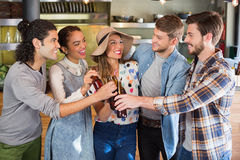 Friends toasting beer bottles in restaurant. Happy friends toasting beer bottles in restaurant Stock Images
