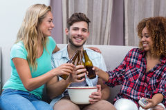 Friends toasting beer while watching soccer match Royalty Free Stock Image