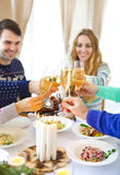 Friends toasting with champagne while having Christmas dinner Royalty Free Stock Images