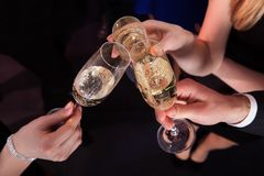 Friends toasting champagne at nightclub. Cropped image of friends toasting champagne flutes at nightclub Stock Image