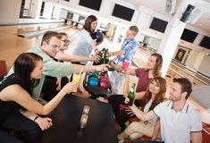 Friends Toasting Drinks in Bowling Club. Group of young friends toasting drinks in bowling club stock photo