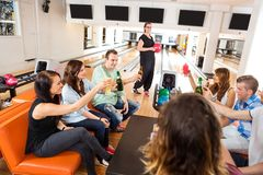 Friends Toasting Drinks in Bowling Club. Group of young friends toasting drinks in bowling club stock photos