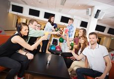 Friends Toasting Drinks in Bowling Club. Group of young friends toasting drinks in bowling club royalty free stock image