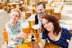 Friends toasting in garden restaurant Royalty Free Stock Images