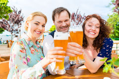 Friends toasting in garden restaurant Stock Image