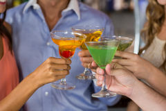 Friends toasting martini and cocktail glass. Close-up of friends toasting martini and cocktail glass in bar stock photos