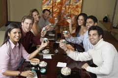 Friends Toasting Saki Cups Stock Photography