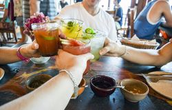 Friends toasting with tropical drinks. Friends toasting, saying cheers holding tropical blended fruit margaritas.  Watermelon and passionfruit drinks Royalty Free Stock Images