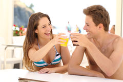 Friends toasting in summer vacation. In a restaurant terrace on the beach Stock Photos