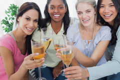 Friends toasting with white wine at the camera. At home on couch Stock Photos