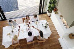 Friends Toasting Wine Across Table At Dinner Party. High angle view of multiethnic friends toasting wine across table at dinner party Stock Photo