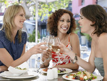 Friends Toasting Wine At Outdoor Cafe. Happy multiethnic female friends toasting wine at outdoor cafe Royalty Free Stock Photography