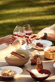 Friends toasting with wine over a spaghetti meal. Outdoors at a picnic table in the garden clinking glasses as they celebrate together Stock Photography